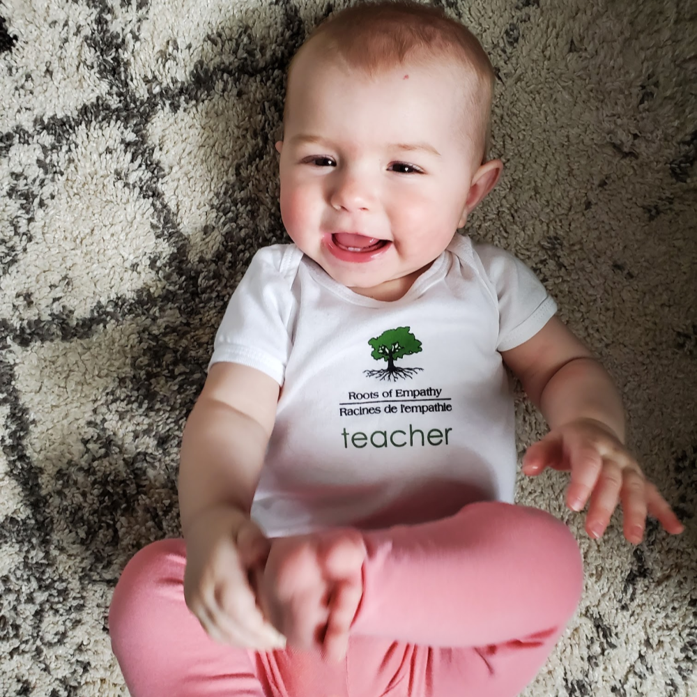 Baby Arden lays on her back on the rug, smiling at camera, wearing her teacher tshirt and pink leggings. She's playing with her foot.