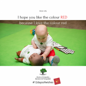 """A baby plays with a baby doll. The caption reads """"I hope you like the colour red because I love the colour red"""""""