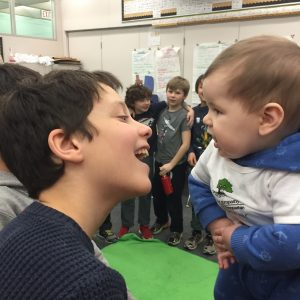 A boy and a baby interact.