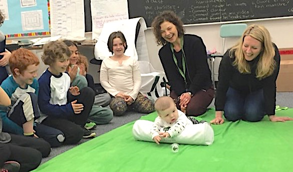 Baby on green blanket in a classroom. People sit around him watching him.