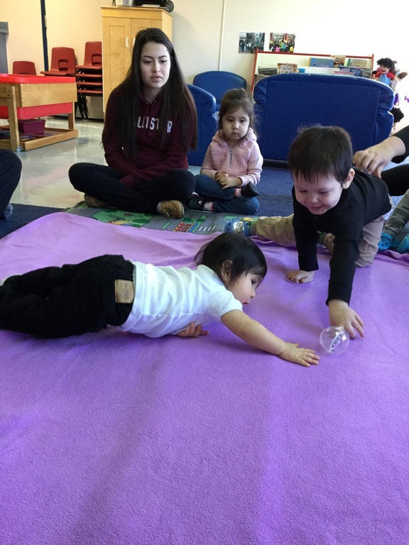 A student and baby play on the purple blanket, passing a clear plastic ball back and forth.
