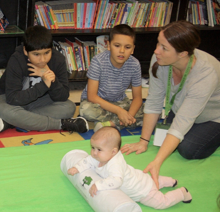 A baby leans against a support pillow while a mother speaks to the class gathered around the green blanket.