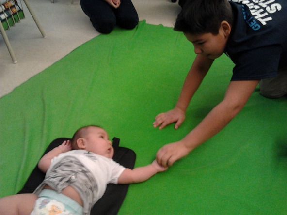 Grade 7/8 classroom with Baby Luke, Christian Island Elementary, Beausoleil First Nation. He holds the hand of a student from the class.