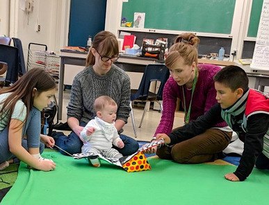 A baby looks at a picture book with teacher, instructor, and students on the green blanket. First Nations School of Toronto
