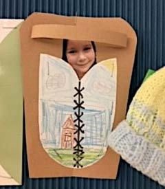 A student from First Nations School of Toronto created an artwork of a drawing of a cradleboard with a cut out of her face.