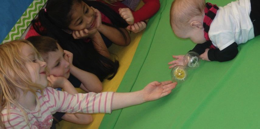 A young girl passes a ball to a baby on the green blanket while other students watch them play.