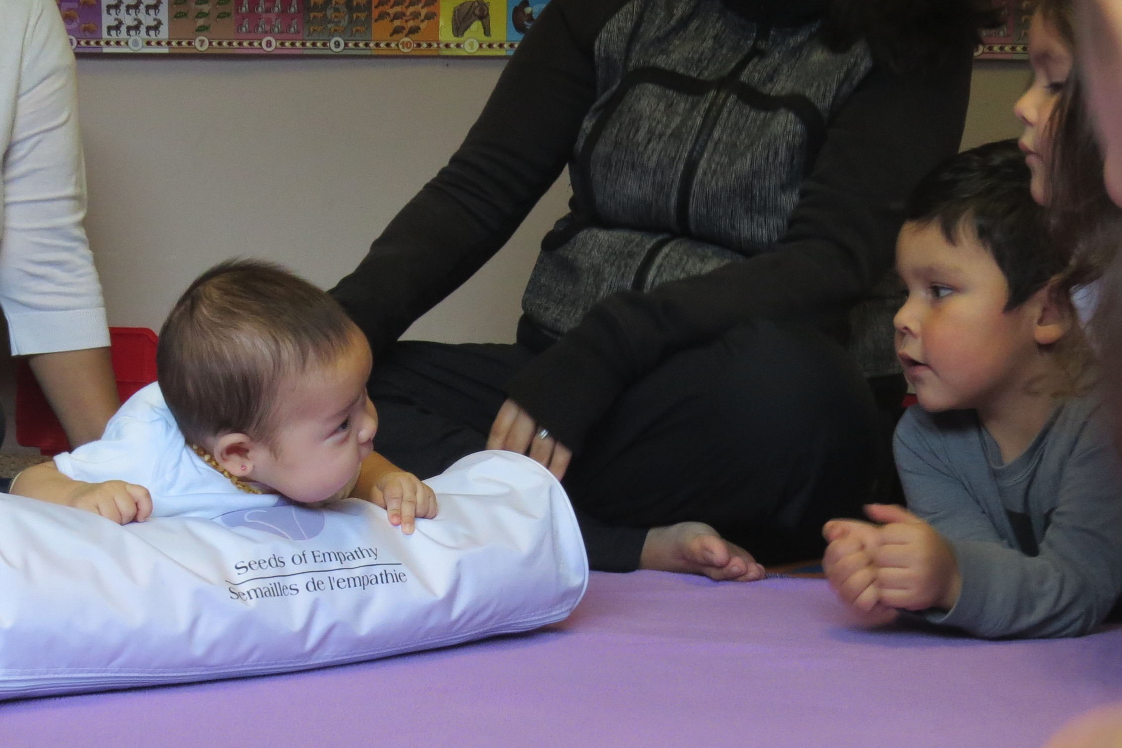 A student watches from the edge of the lavender blanket as a baby supported by a log pillows looks back at him.